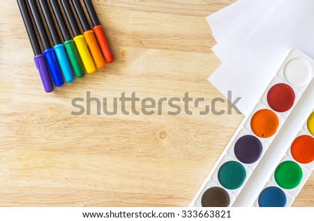Colored felt-tip pens, lying like rainbow, white paper and watercolor on wooden background - stock photo