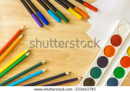 Colored felt-tip pens, lying randomly colored pencils, white paper and watercolor on wooden background - stock photo