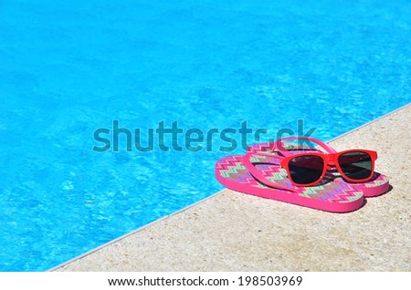 Colored flip-flops and sunglasses beside the swimming pool  - stock photo