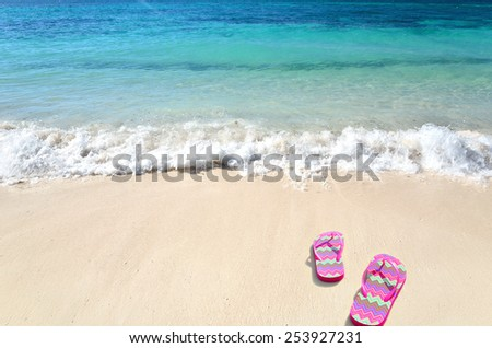 Colored flip flops at sunny beach -- Tropical beach vacation and travel concept - stock photo
