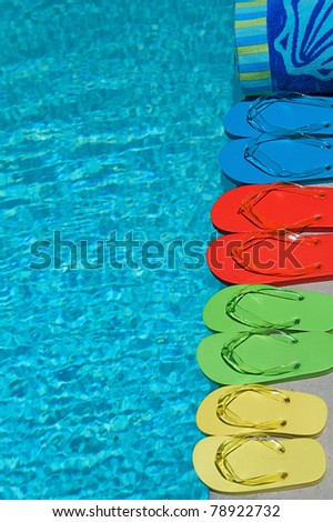 Colored flipflops of a family of four by the swimming pool - stock photo