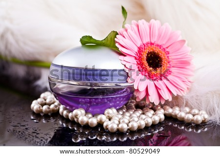 colored glass bottles exclusive perfume on the background of feathers and pearls and flowers with water drops - stock photo