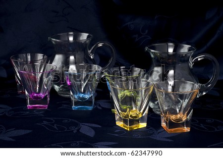 Colored glass jug and glasses on a dark background