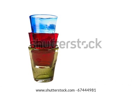 Colored glass stacked on each other. Red, blue and green. isolated over white background