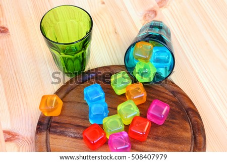 Colored glasses and reusable cubes for freezing and cooling beverages. Kitchen or dinning room composition on the wood