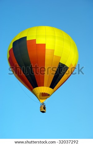 Colored Hot Air Balloon on solid blue sky background