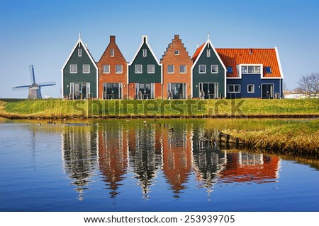 Colored houses of marine  park in Volendam reflected in the water on a winter morning, Netherlands - stock photo