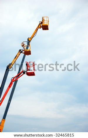 Colored  hydraulic cherry pickers over blue sky - stock photo
