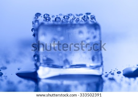 Colored ice cubes on wet glass table. Selective focus. Shallow depth of field. - stock photo