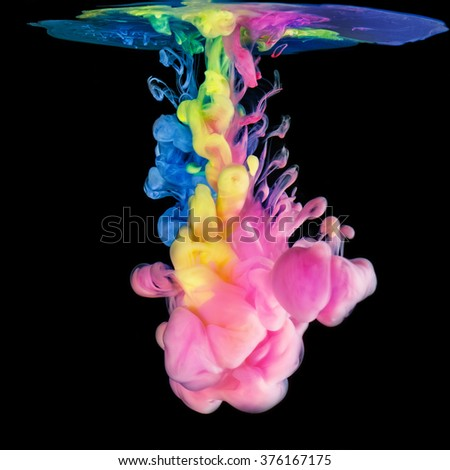 Colored ink drops in water on black background - stock photo