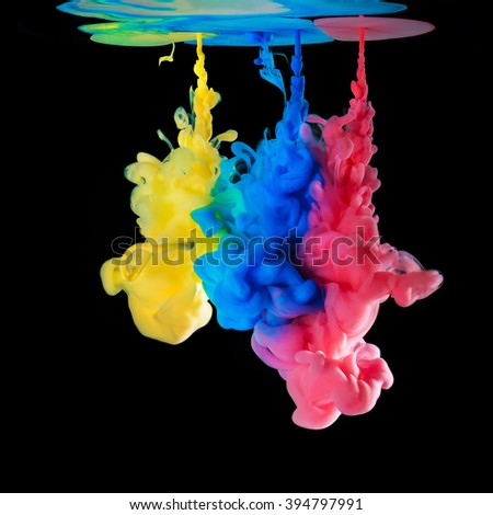 Colored ink drops in water on black background