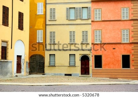 Colored Italian houses overlooking little square with cobblestones - stock photo