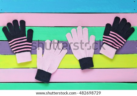 colored knitted gloves on painted wooden background