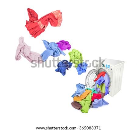 Colored laundry flying from washing machine, isolated on white background - stock photo