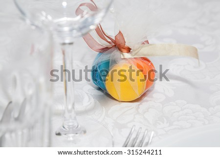 Colored macarons on wedding table with ribbon - stock photo