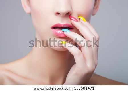 Colored manicure, Woman face with rainbow makeup and manicure - stock photo