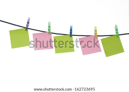 Colored memos on string with clothespin isolated on white background