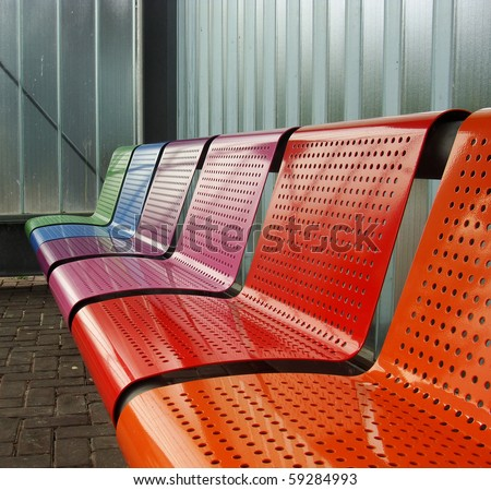 colored metal bench at a tram bus train stop - stock photo