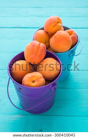 Colored metal buckets with ripe apricots on colored wooden table/Colored metal buckets with apricots - stock photo
