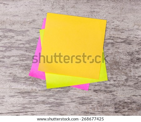 colored note paper on wooden background - stock photo