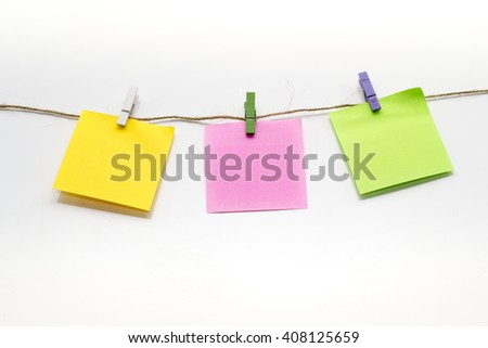 colored notes hanging from a rope on a white background