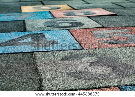 Colored numbered rubber floor tiles for playing hopscotch - stock photo