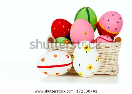 Colored painted eggs in basket on white background