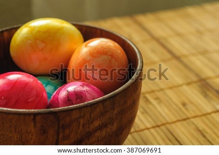 colored, painted eggs in wooden bowl on bamboo napkin. For Easter