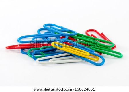 Colored paper clips on a white background. - stock photo