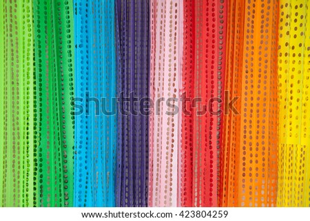 Colored paper confetti with holes. Confetti for celebration. View from above. Wooden background. Light wood. - stock photo