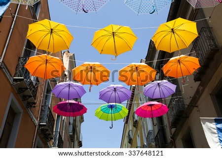 Colored parasols in the streets of Iglesias, Sardinia, Italy - stock photo