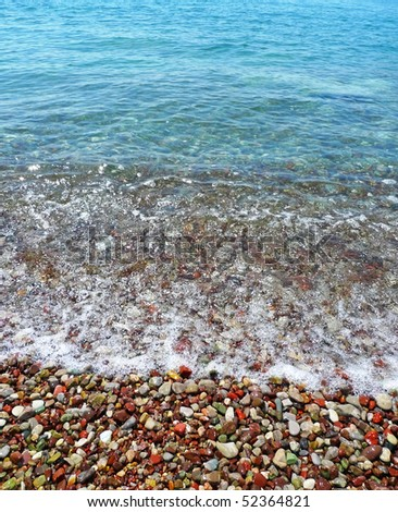 Colored pebbles on the beach and sea wave - stock photo