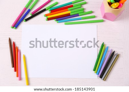 Colored pencils and blank paper sheet on wooden table - stock photo