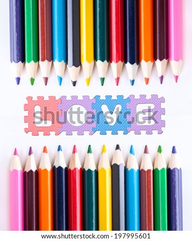 Colored pencils and LOVE word written with puzzle pieces - stock photo