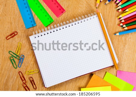 Colored pencils and notepad on wooden table - stock photo
