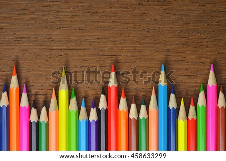 Colored pencils  are zigzag on the wooden background