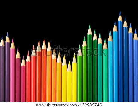 Colored pencils arrangement on black background - stock photo