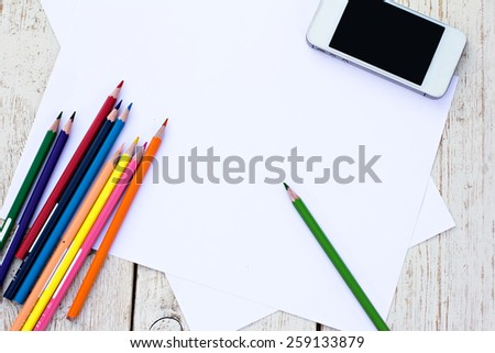Colored pencils, cell phone and paper on the desk - stock photo