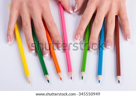 Colored pencils in a beautiful female fingers. Beautiful french manicure with pencils. - stock photo