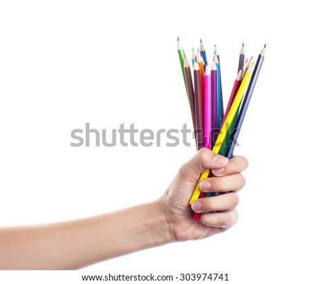 Colored pencils in a female hand on a white background . - stock photo