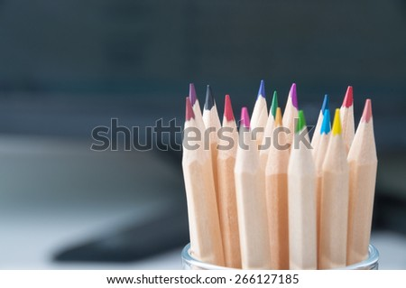 colored pencils in a glass jar shot from the front - stock photo