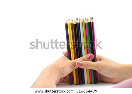 Colored pencils in female hand on white background