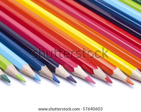 Colored pencils in formation pointing to the right. - stock photo