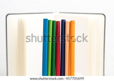 colored pencils in front of a notebook /  office supplies / back to school .