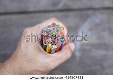 colored pencils in hand - stock photo