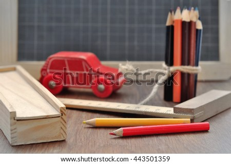 colored pencils on a slate  with box , rule and toy  on a wooden background - stock photo