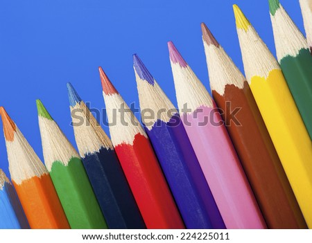 Colored pencils on blue background - stock photo