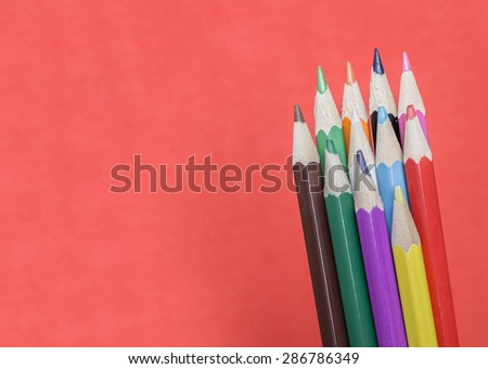 Colored pencils on red background - stock photo