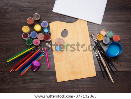 colored pencils paint brush against the dark table - stock photo