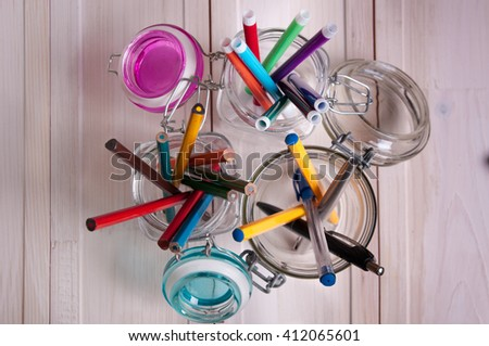 colored pencils, pens and markers in glass bank on a table - stock photo